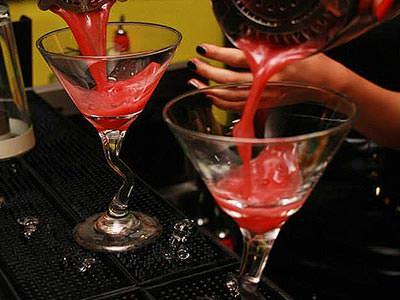 Two martini glasses being filled with red cocktail from metal cocktail shakers