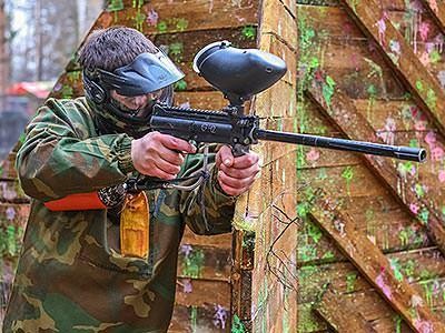 A man wearing a paintball mask and overalls aiming a paintball gun in front of a paint-splattered fence