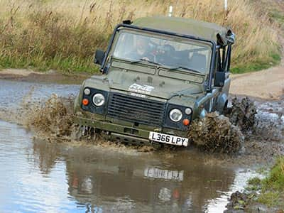 A 4x4 vehicle driving through a large puddle on a muddy track and spraying water