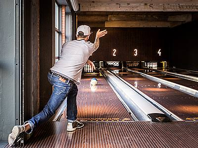 A man throwing a bowling ball down an alley top the pins standing up