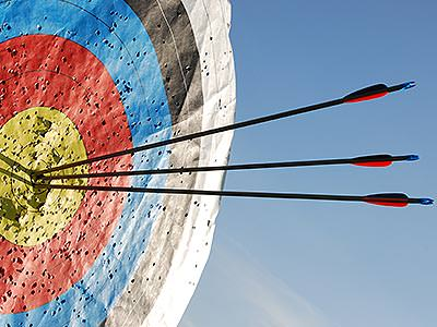A large archery target with three arrows stuck in it