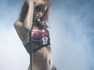 A woman posing in pink lingerie, surrounded by white smoke
