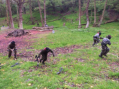 Four people running in a wooded area with paintball guns in their hands