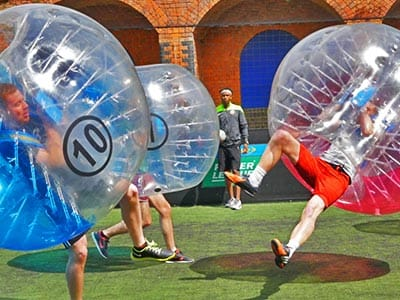Two people falling over in inflatable zorbs on an outddor field