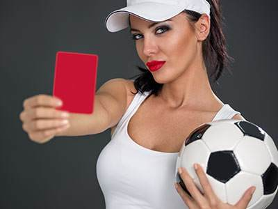 A woman in a white vest and visor, holding a black and white football and a red card in front of her to a grey backdrop