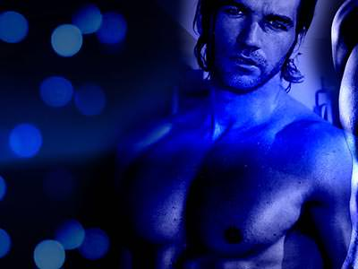 A topless man dimly lit with blue lights