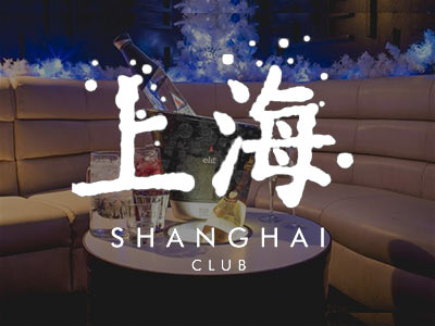A booth area with drinks on a round table and the Shanghai logo over