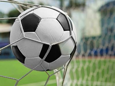 A football stretches the netting of a goal