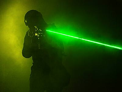 A man surrounded by smoke aims a gun emitting a visible green laser past the camera