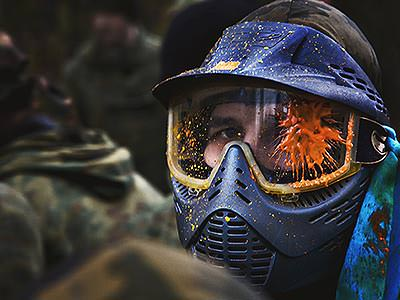 A man wearing a full-face paintball mask, with an orange paint splat over his left eye