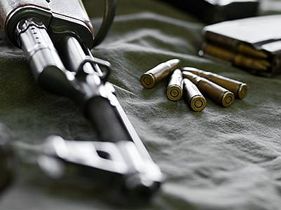A Kalashnikov style rifle lying on cloth with the barrel visible and ammunition scattered nearby