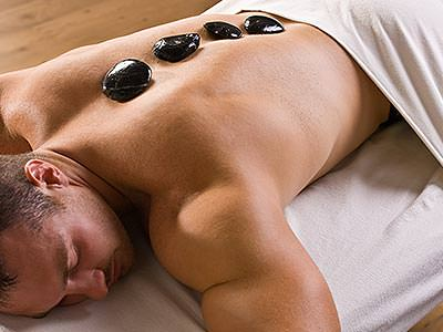 A topless man lying face down with four black stones placed on his back