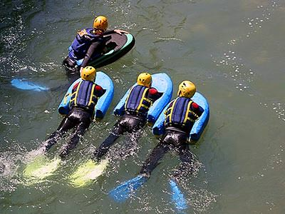 A group of people paddle through water, holding onto floats