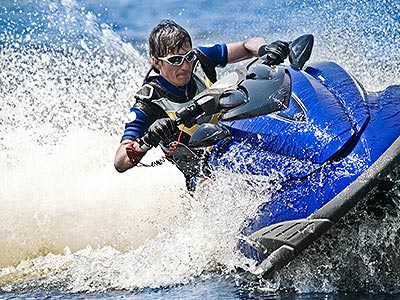 A man performs a sharp turn on a blue jet ski, spraying water out behind him