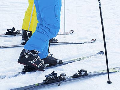 Two pairs of legs wearing ski boots, in the process of putting on skis