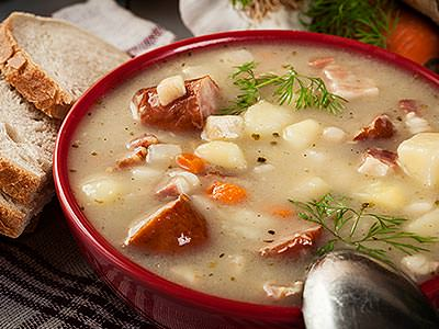 A bowl of vegetable and meat soup with bread