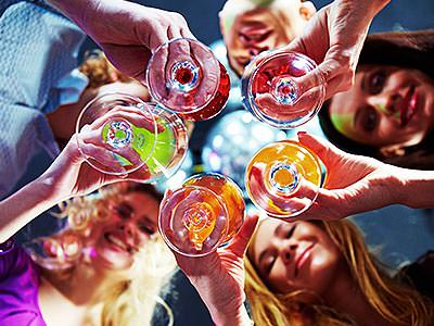 A group of women clinking multicoloured drinks together, shot vertically up from floor level