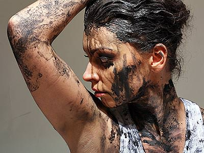 A woman posing with her arm up and looking away, covered in mud