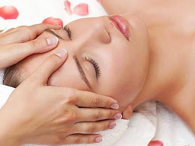 A close up of a woman's face as she lies on a white towel receives a massage to the head