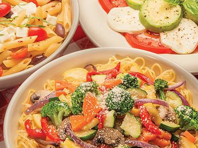 Two plates of pasta and a plate of tomato and mozzarella salad