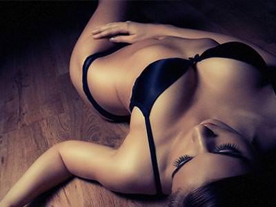 A woman reclining on a wooden floor in underwear