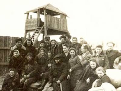 A black and white historic image of a large group of people in front of a guard tower
