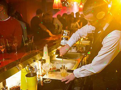A bartender making a drink behind a busy bar