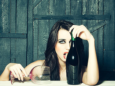 A woman holding an empty wine glass and licking a wine bottle