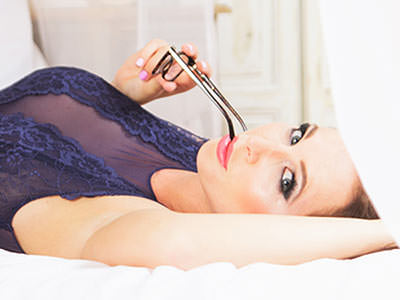 A woman lying on a bed, wearing navy lingerie, and holding some glasses to her mouth in a seductive way