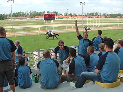 Some lads all wearing the same blue and raglan tops, at the races, with horses running in the background