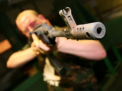 A man wearing camouflage and aiming his gun just beyond the camera