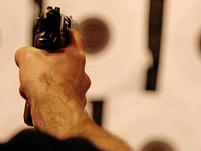 A person's hand firing a gun, with the background out of focus