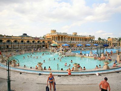 The exterior pool of Szechenyi Thermal Baths, crowded with people, with buildings in the background, during the day