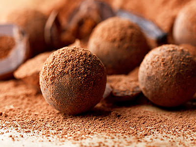 Close up of chocolate truffles on a table covered with cocoa powder