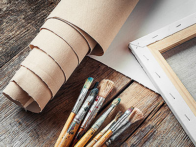 An artist's paint brushes and canvas laid out on a wooden table