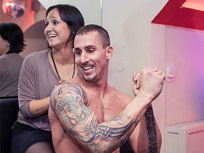 A tattooed man flexing his muscles as a woman touches him from behind