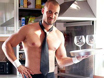 Close up of a man with a naked torso, wearing a tie and apron, holding up a tray with two empty wine glasses