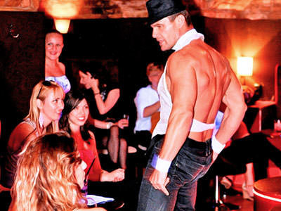 Close up of a male stripper in jeans, standing in front of a group of women sat down