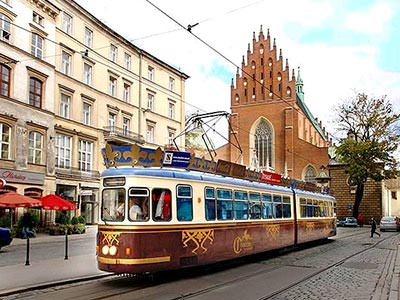 A tram on the street with buildings in the background
