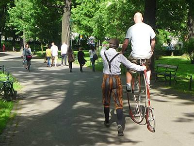 The back of a man riding a penny farthing with an instructor holding him
