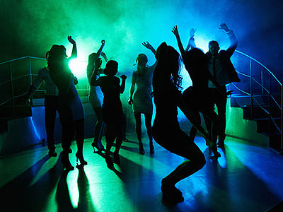 People dancing on a club dancefloor to a backdrop of green and blue light