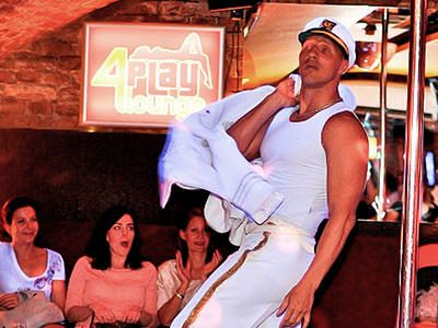 A male stripper dressed as a sailor performing to three women looking on