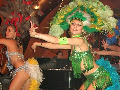 Two women dressed in carnival clothing, dancing in a small venue