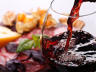A glass of red wine being poured with food in the background