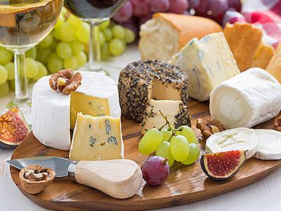 Different types of cheese served on a wooden board, with grapes in the background