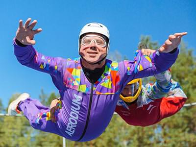 A man in a purple skydiving suit, freefalling on an outdoor simulator
