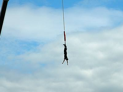 A man hanging from a bungee to a backdrop of the sky