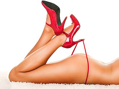 A woman's red stiletto heels hooking the strap of a red thong on a semi-naked woman's body