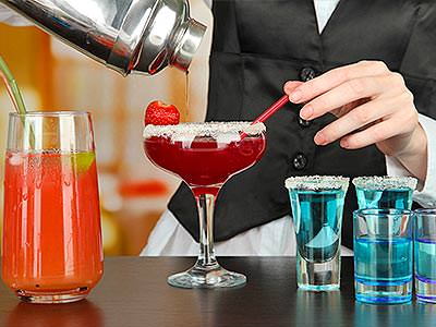 A bartender pouring out a red cocktail into a full martini glass, with blue shots on one side and an orange drink to the other side