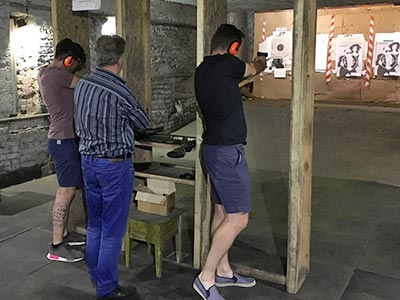 Two men with an instructor, aiming guns at a target